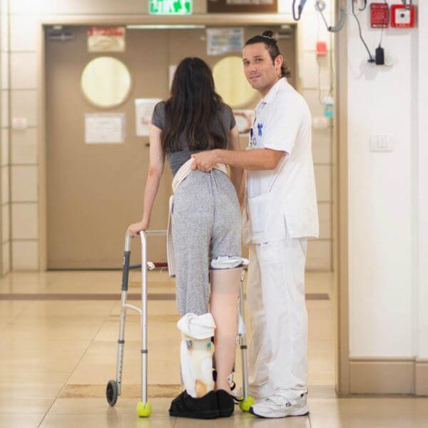 אח מסייע למטופלת ללכת עם הליכון - גולדן קייר , מרכזי שיקום