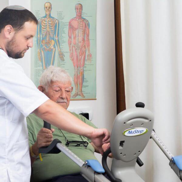 מטפל מכוון מכשיר אימון עבור מטופל בגולדן קר - מרכזי שיקום יום במרכז